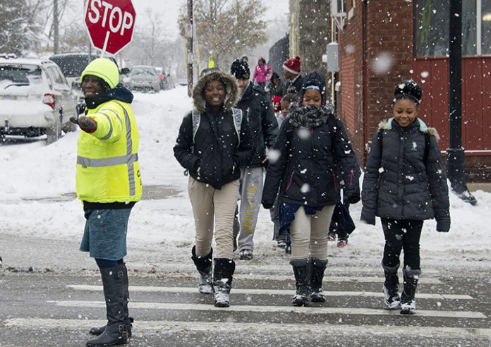 Kattie Eason makes sure all traffic has stopped on Wealthy Street to make way for eighth-graders (from left) Sharkia Caldwell, Zaionna Love and Kalyce Russell