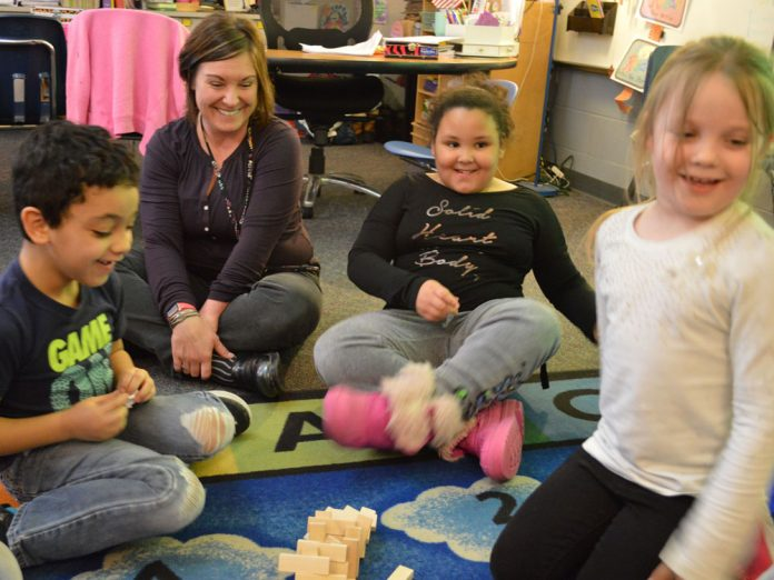 Teacher Jennifer Blackburn joins the fun with her students as a Jenga tower falls during indoor recess
