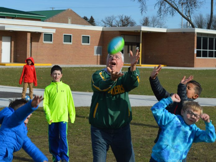 """Volunteer grandparent Ernie Sandona, affectionately called """"Papa Belly Floppa,"""" shows his football prowess at Central Elementary School recess"""