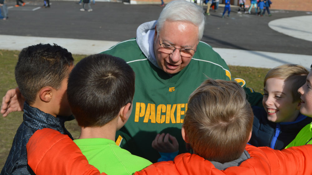 Grandparent Ernie Sandona, a playground volunteer, huddles with Central Elementary School students