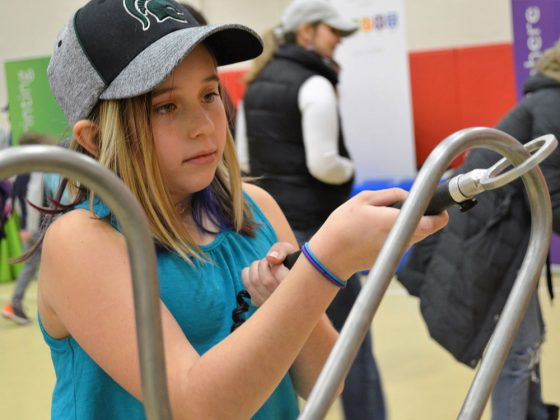 Fourth-grader Carol Carothers tries to thread a metal ring along a course without touching the metal