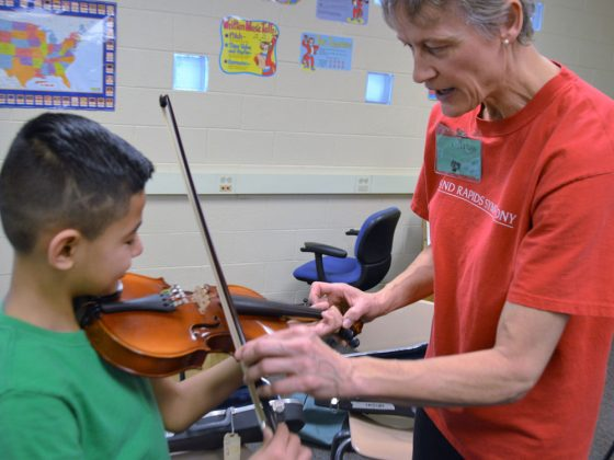 Angel Gonzalez tries to play a violin with guidance from Linda Nelson, violinist with the Grand Rapids Symphony