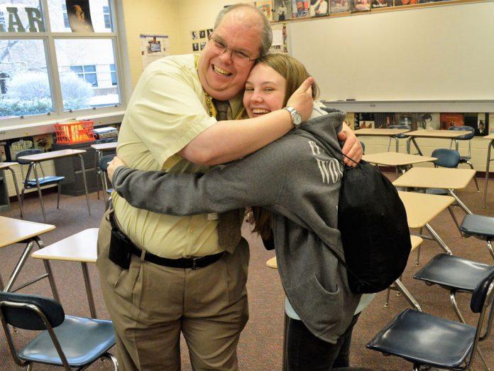 Hugs from students like Allison Klimek are nothing unusual for English teacher David Lyons