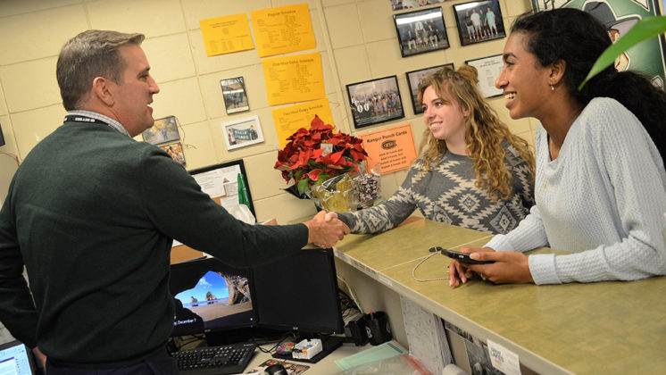 Superintendent Dan Behm, filling in for the athletic secretary, is interviewed by reporter Krystal Koski as editor-in-chief Reena Mathews, right, takes photos