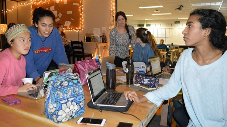 Editor-in-chief Reena Mathews, far right, edits copy while reporters work on their articles; foreground, from left: Irene Yi and Susannah Bennett