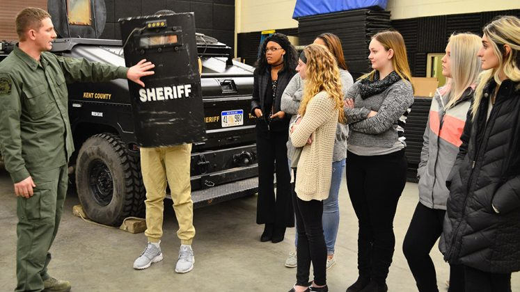 About a dozen students spent Groundhog Shadow Day at the Kent County Sheriff's Department; here, tactical team member Sgt. Justin Deboode shows some of his equipment