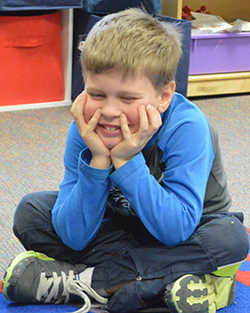 """Emmons Lake kindergarten student Drake VanLente demonstrates """"not following the group plan"""" by staying seated while his classmates return to their desks"""