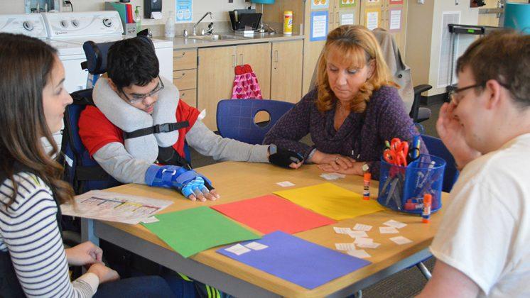 From left, teacher Courtney Redmond, junior Roger Swets, nurse Marie Groot, and senior Brendan Dolan work on a Social Thinking activity