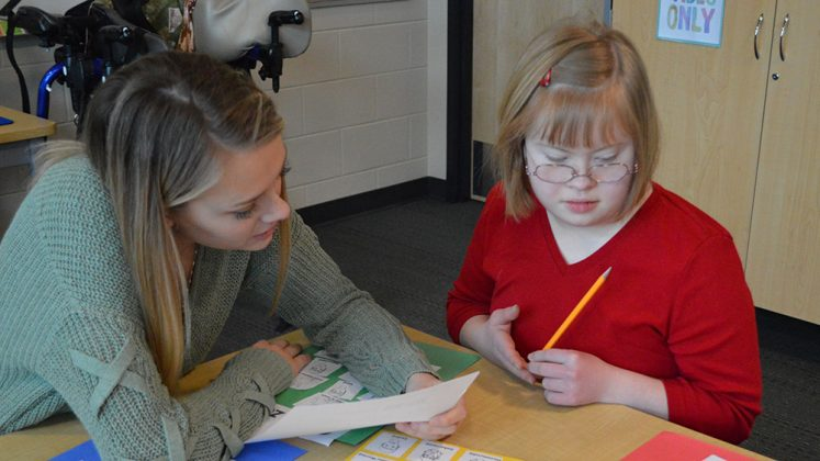 From left, senior Lizzy Klein works with senior Ruthie Roelse on identifying emotions