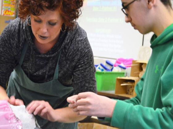 Art teacher Whitney Goulooze helps Martin Esho smooth plaster on Matthew Bahman's face