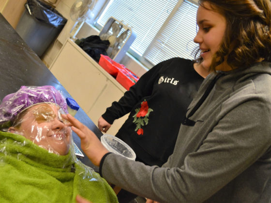 Seventh-grader Claudia Swenson applies petroleum jelly to classmate Arian Watkins' nose before setting plaster