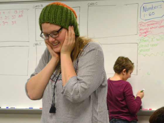 Rachel Walker, a Grand Rapids Community College student helping at the STEM event, turns her back so she wouldn't see the numbers students picked in the Mathematical Magic and Mysteries station
