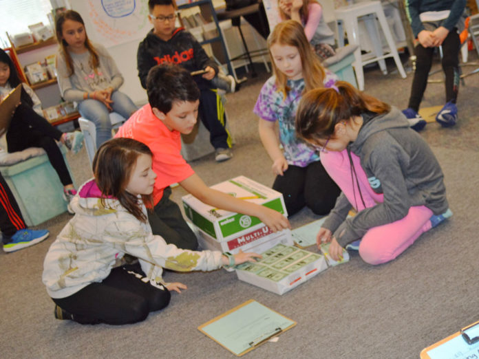 """Bridget Bennett's fourth-graders use the """"fishbowl"""" style of problem-solving to figure out how to fit a million dollar bills into a box. Students are from left: Aubrey Sieler, Sam Bauchan, Fiona Overdevest and Mady Scarlato"""