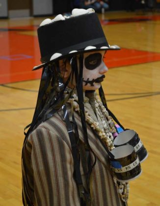 """One of the scariest costumes was worn by the witch doctor from Corunna, a team which Judy Flynn coached. She's been coaching for 30 years, getting involved when her son was in seventh grade, and he helps her coach today. """"I thought I'd be done with it when the kids were done, but these kids get too much from program. I couldn't give it up,"""" Flynn says"""