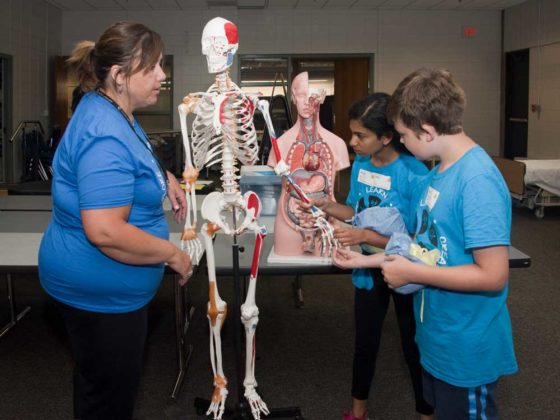 Nurse and instructor Jen Gebhardt teaches Shreya Anil, eighth grade, Forest HIlls Northern Hills Middle; and Rhone Spink-Knight, seventh grade, EGR Middle; about the skeleton