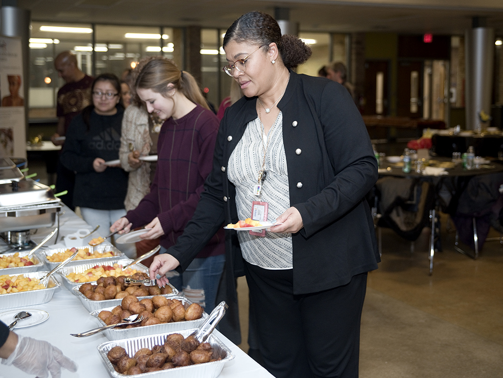 Maleika Joubert Brown, GRPS director of Equity and Inclusion, helps herself to dessert after an African cuisine meal that included a vegetable pepper soup, jollof rice and tomato stew