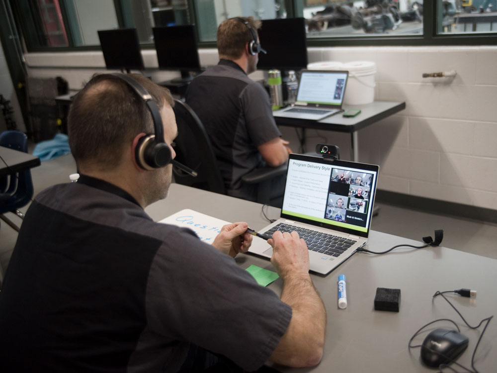 """Auto Tech Instructor Nathan Vannest """"zooms"""" with families at the Virtual Open House with colleague Joshua Denhof in the background"""